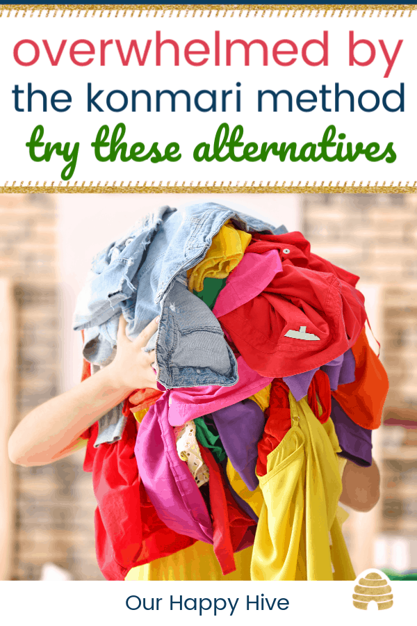 Woman holding pile of colorful clothes indoors with text overwhelmed by the konmari method try these alterntives