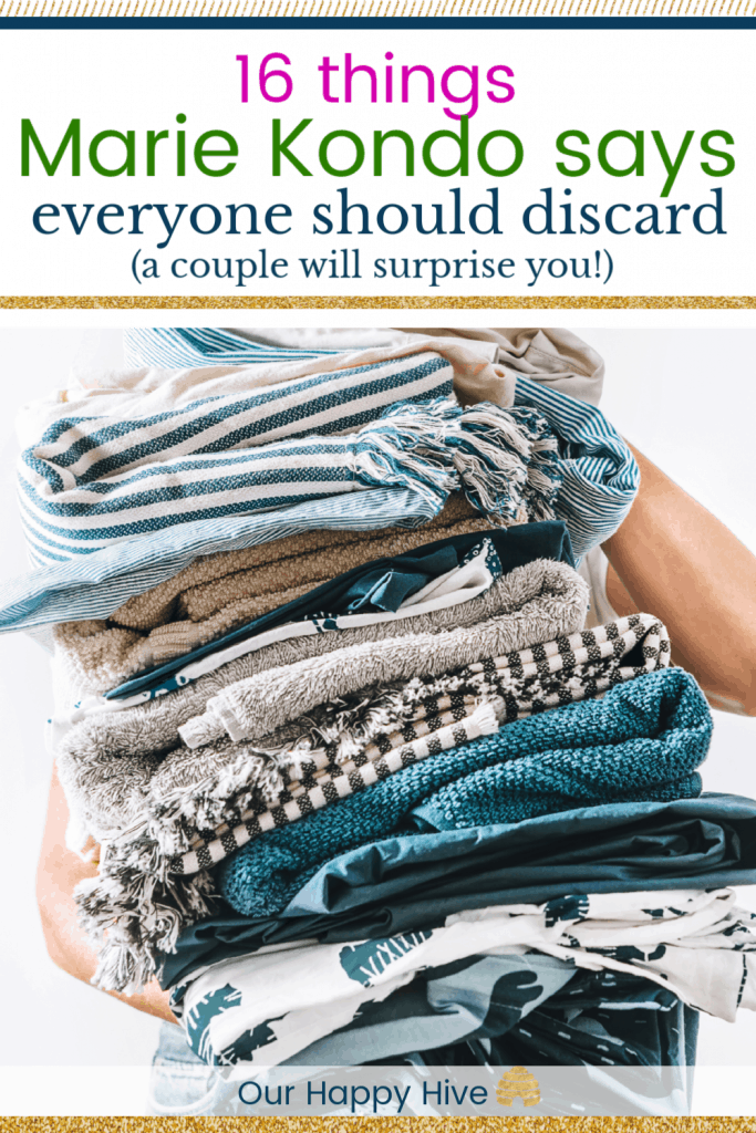 Woman takes in hands big pile blue and beige laundry with text 16 Things Marie Kondo Says Everyone Should Discard