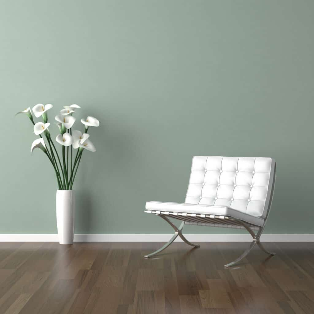 white modern chair and a vase of calla lilies on a pale green wall