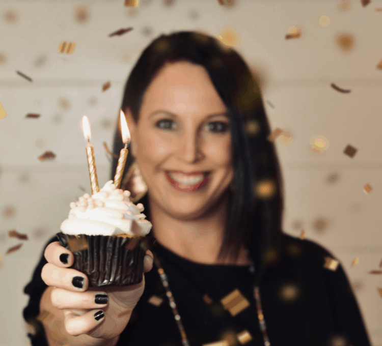 Girl holding a cupcake with two candles on it.