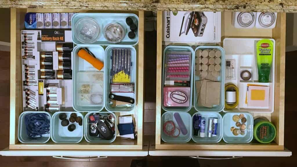 side by side two organized drawers with containers for each item in the drawer
