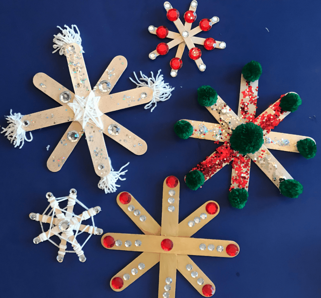 a variety of brightly colored diy popsicle stick snowflakes