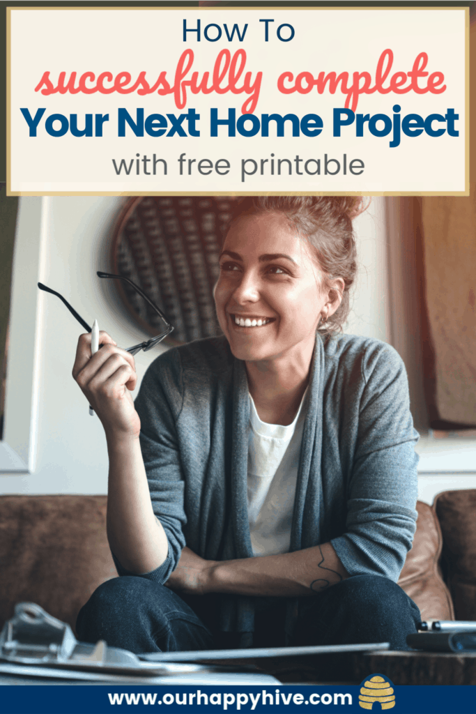 Woman thinking bout her next home improvement project. Working on a project plan to reduce overwhelm and actually complete the project. Woman sitting at a desk with a smile on her face with text how to successfully complet Your Next Home Project with free printable.