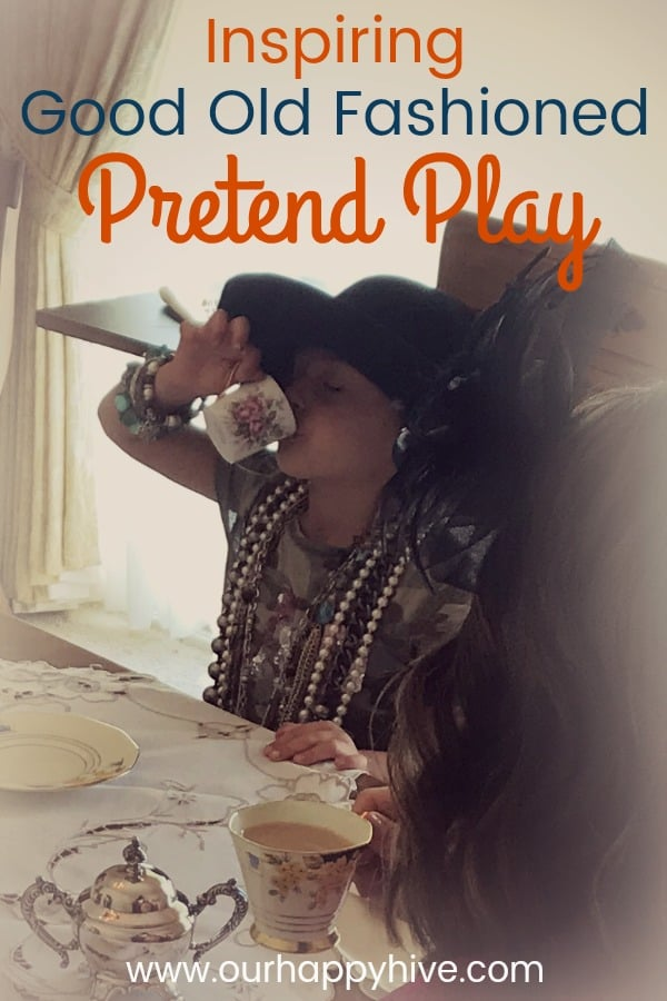 Preschooler dressed up in a broad brimmed hat with lots of jewelry on while sipping tea with text Inspiring Good Old Fashioned Pretend Play