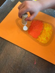 Candy Corn Printable being painted by a preschooler with a wine cork stamp.