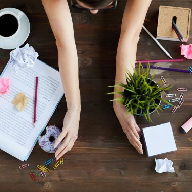 Woman sorting out mess on working table, moving stationery, documents, food and plant