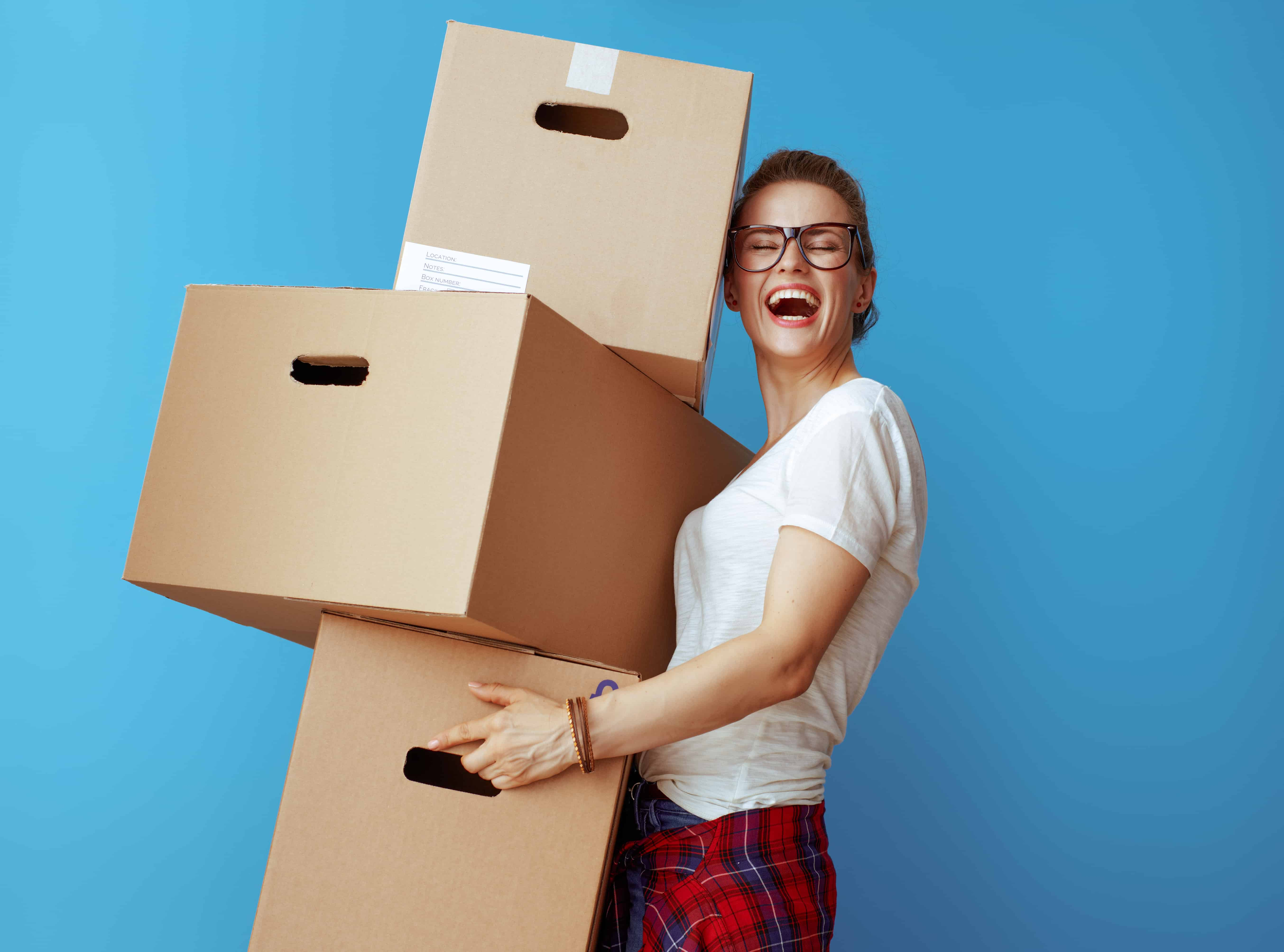 Woman holding boxes and smiling after decluttering and preparing for a move.