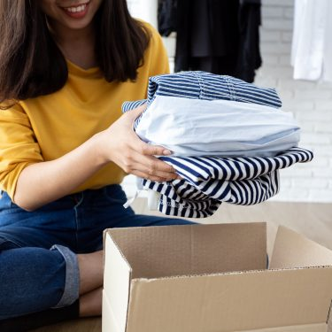 Woman holding Clothes with Donate Box In her room.