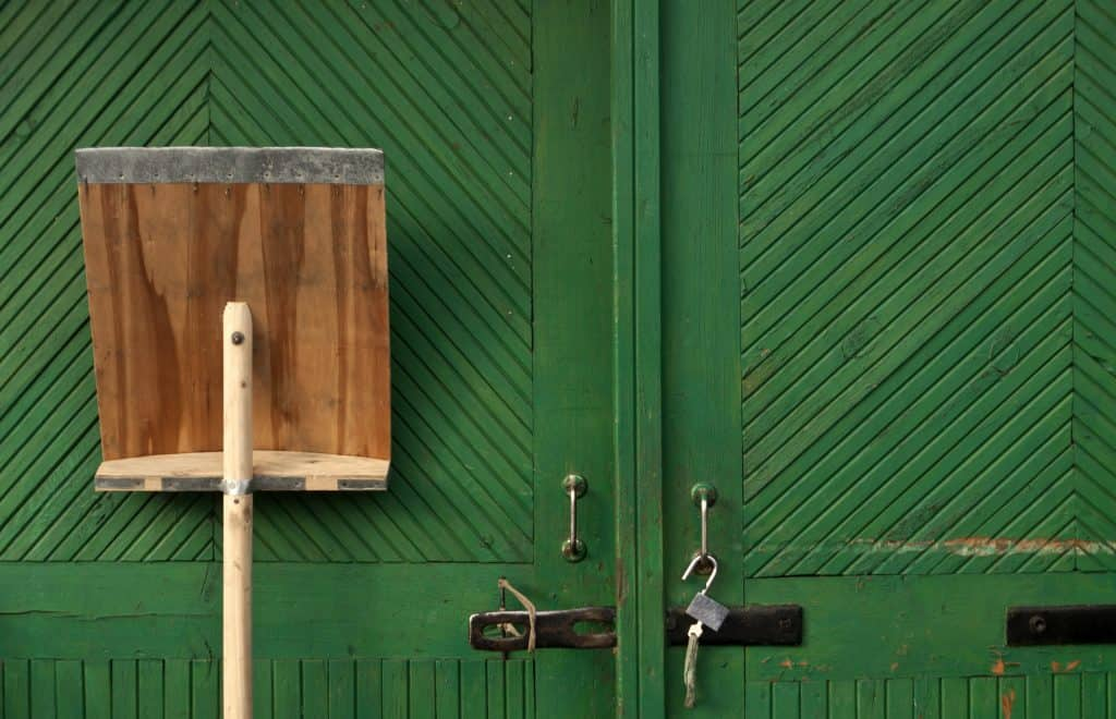 Wooden snow shovel in fron of green hangar door. Tools.