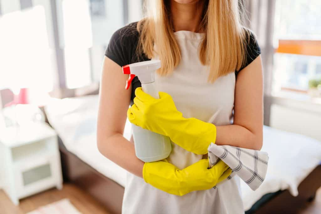 Woman wearing white apron and rubber protective yellow gloves, holding rag and spray bottle detergent.