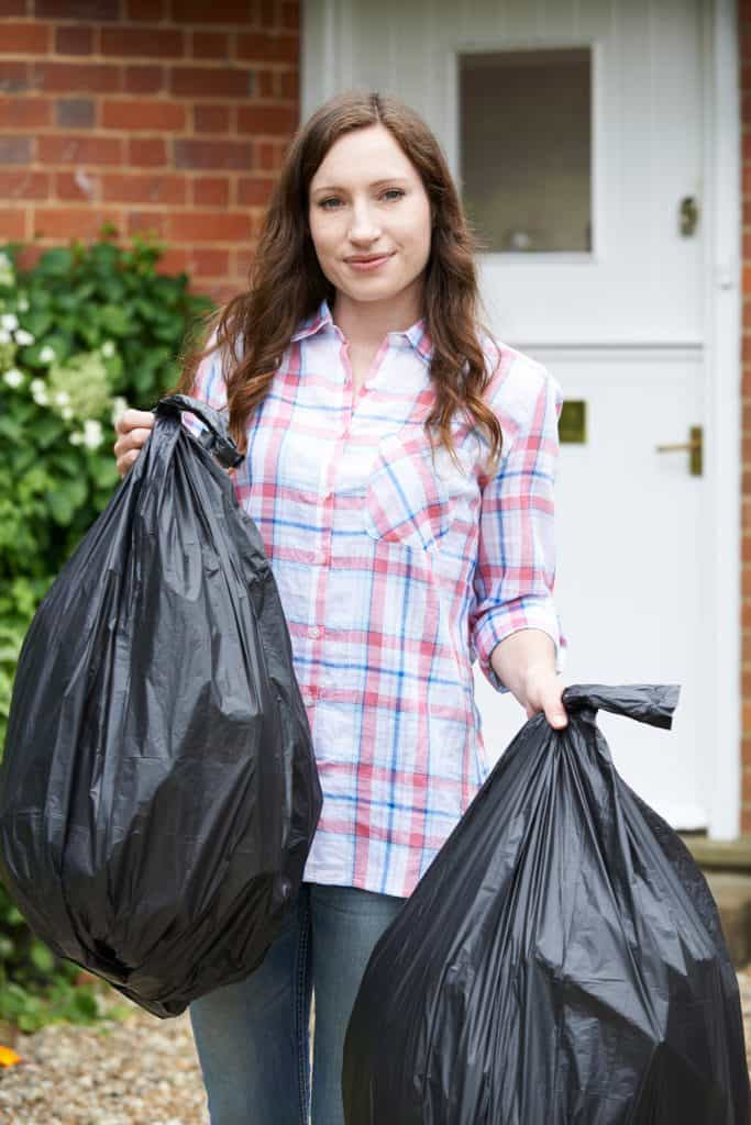 Woman with bags of items she's discarding after decluttering