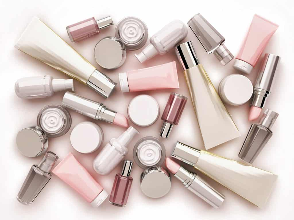 Cosmetic cream, lipstik and perfume on white background. Top view.
