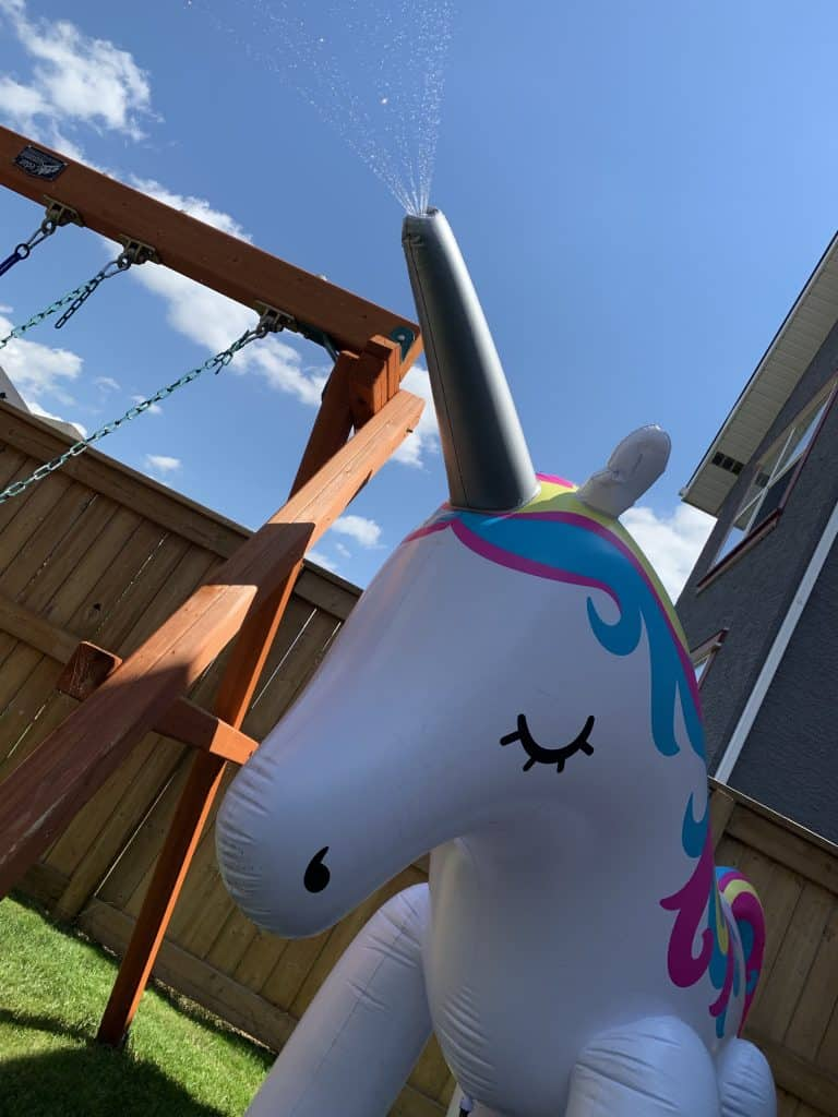 Unicorn Sprinker in Famiy Friendly Backyard next to swingset.