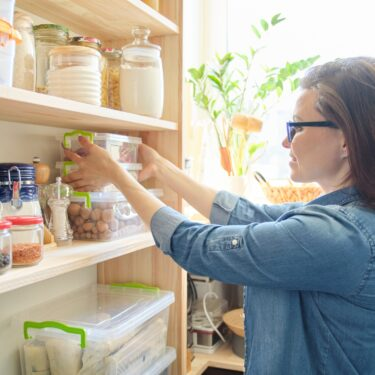 woman standing in front of her organized pantry